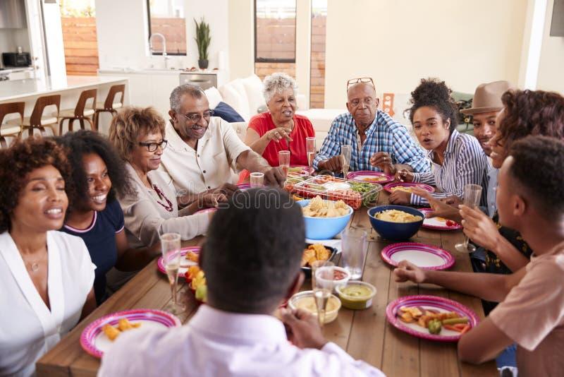 Afrikansk amerikanfamilj f?r tre utveckling som sitter p? matst?lletabellen som tillsammans upp firar, slut fotografering för bildbyråer