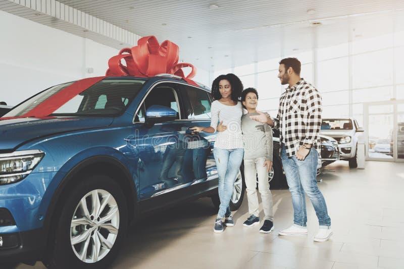 Afrikansk amerikanfamilj på bilåterförsäljaren Avla, modern och sonen nära den nya bilen royaltyfria bilder