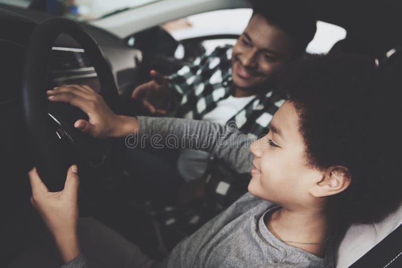 Afrikansk amerikanfamilj på bilåterförsäljaren Fadern och sonen är provet som kör den nya bilen arkivbilder