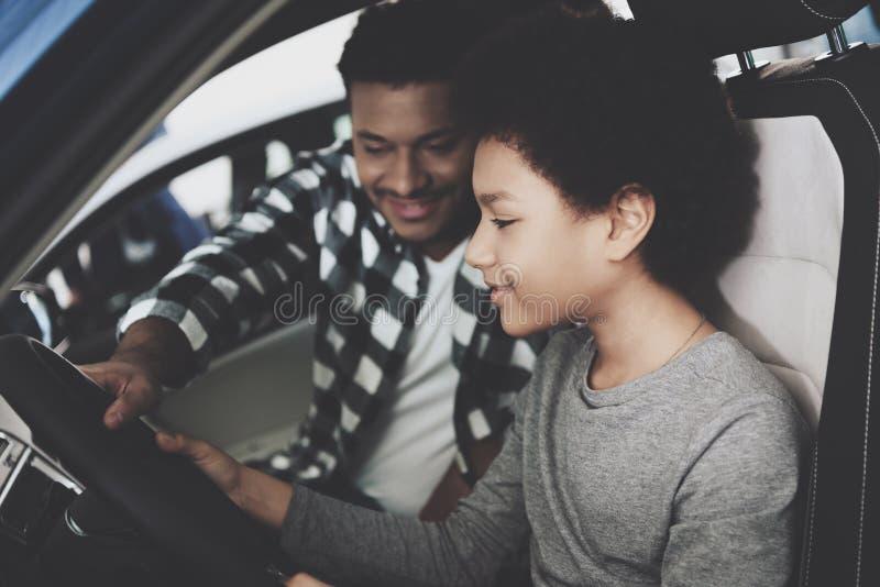 Afrikansk amerikanfamilj på bilåterförsäljaren Fadern och sonen försöker ut den nya bilen royaltyfri bild