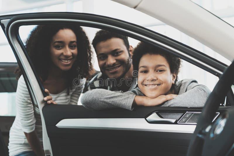 Afrikansk amerikanfamilj på bilåterförsäljaren Modern, fadern och sonen pising i fönster av den nya bilen arkivfoto