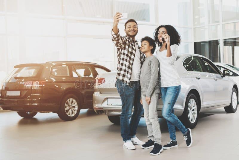 Afrikansk amerikanfamilj på bilåterförsäljaren Modern, fadern och sonen tar selfie framme av den nya bilen arkivfoton