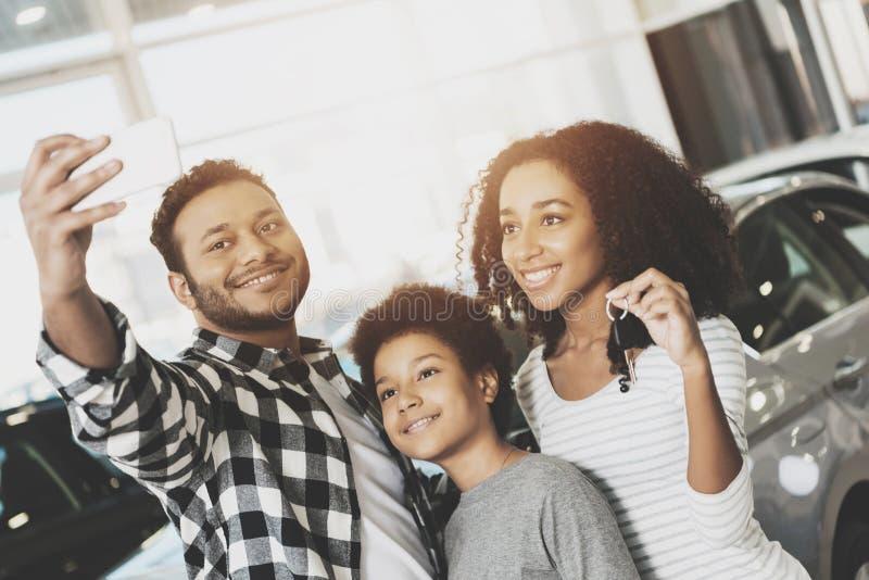 Afrikansk amerikanfamilj på bilåterförsäljaren Modern, fadern och sonen tar selfie framme av den nya bilen royaltyfria foton