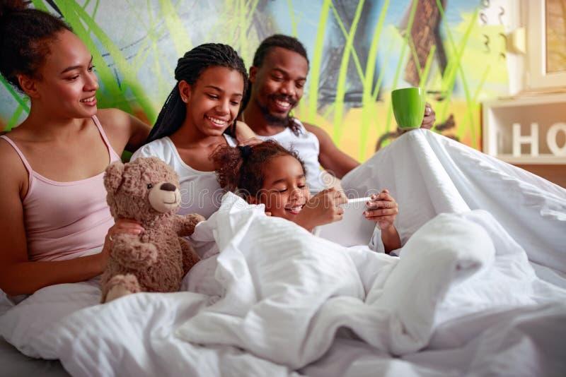 Afrikansk amerikanfamilj som ligger på sovrum i säng arkivfoton