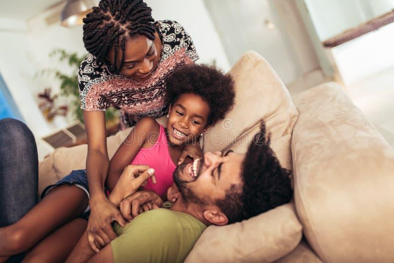 Afrikansk amerikanfamilj som tillsammans spenderar tid hemma royaltyfri fotografi