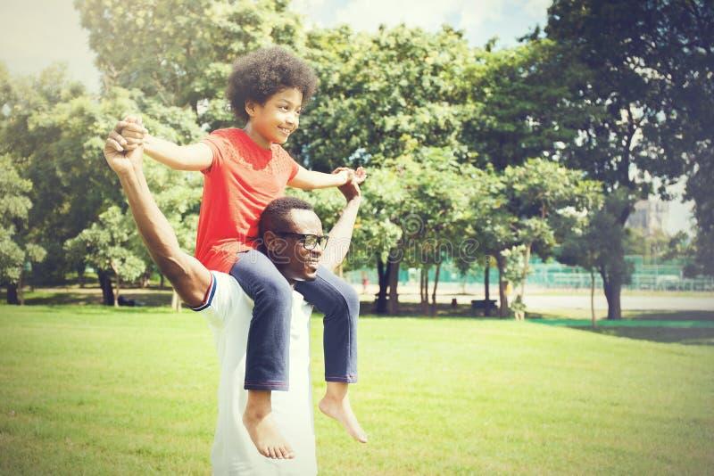 Afrikansk amerikanfamiljen som på ryggen gör och har gyckel i det utomhus-, parkerar under sommar arkivfoto