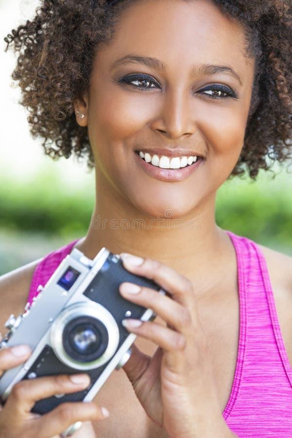 Afrikansk amerikanflicka för blandat lopp med den Retro kameran fotografering för bildbyråer