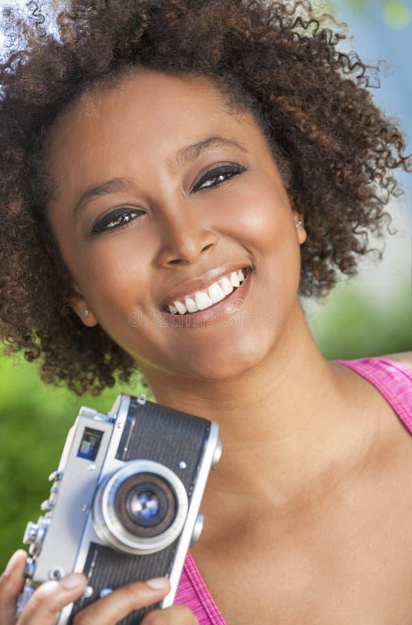 Afrikansk amerikanflicka för blandat lopp med den Retro kameran royaltyfria foton
