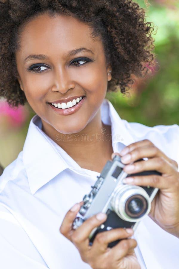 Afrikansk amerikanflicka för blandat lopp med kameran royaltyfria foton