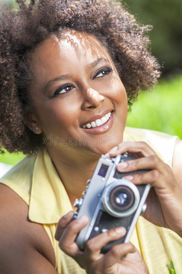 Afrikansk amerikanflicka för blandat lopp utanför med kameran fotografering för bildbyråer