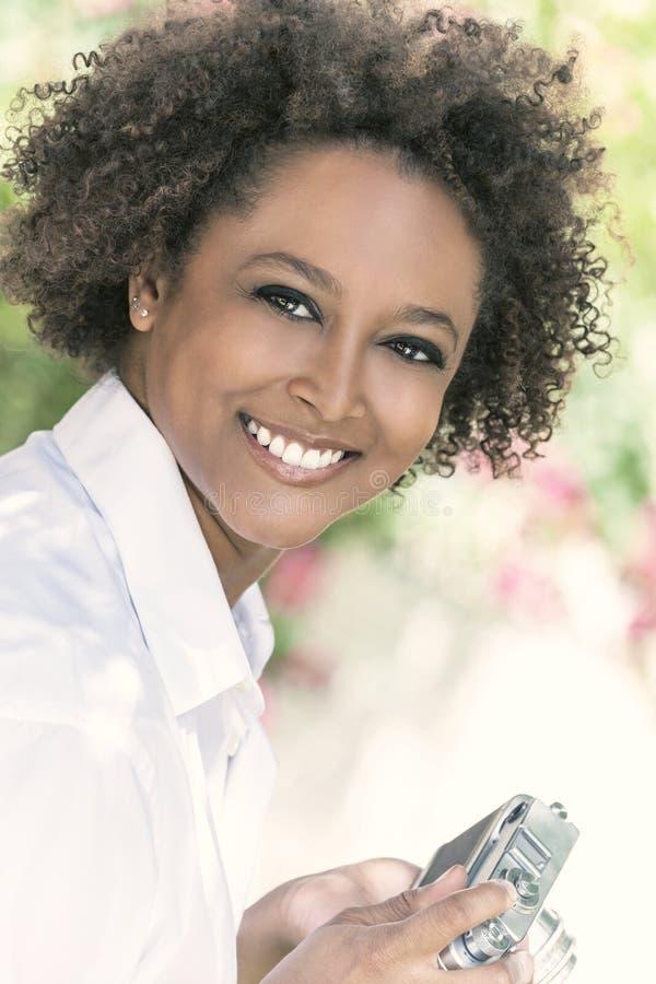 Afrikansk amerikanflicka f?r blandat lopp utanf?r med kameran arkivbild