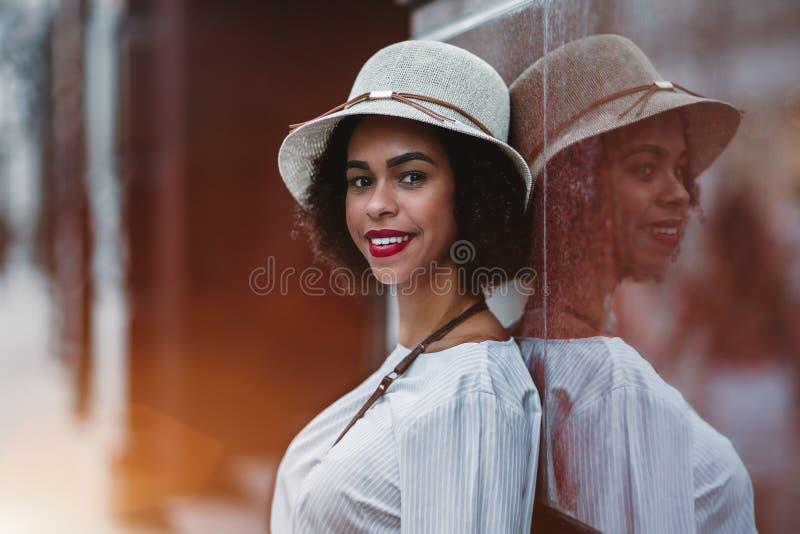 Afrikansk amerikanflicka i hattbenägenheten mot den marable väggen arkivfoton