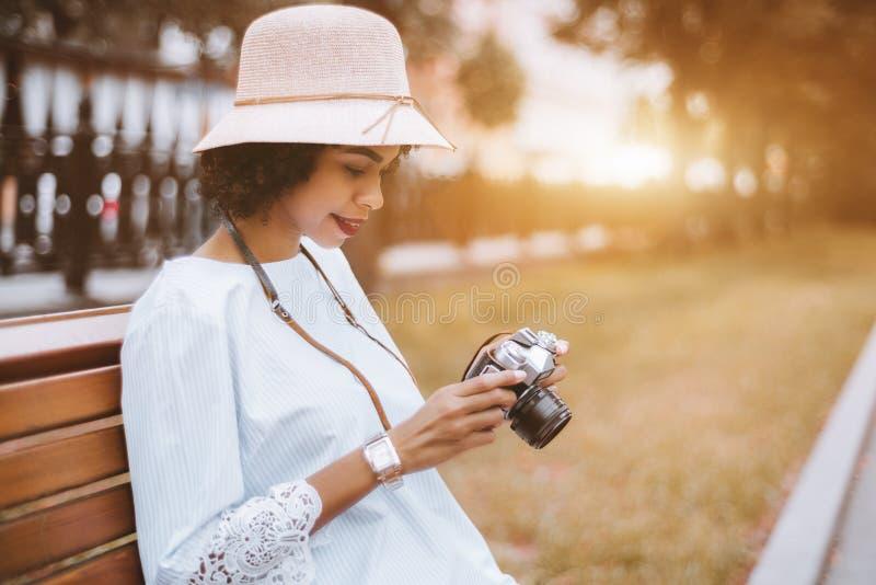 Afrikansk amerikanflicka med den retro kameran på parkerabänken arkivfoto
