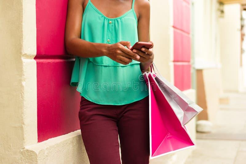 Afrikansk amerikanflicka som överför textMessaging på telefonen som shoppar B royaltyfri fotografi