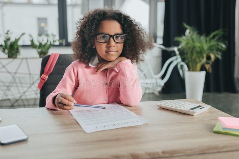Afrikansk amerikanflicka som låtsar för att vara affärskvinna och i regeringsställning gör skrivbordsarbete arkivbild