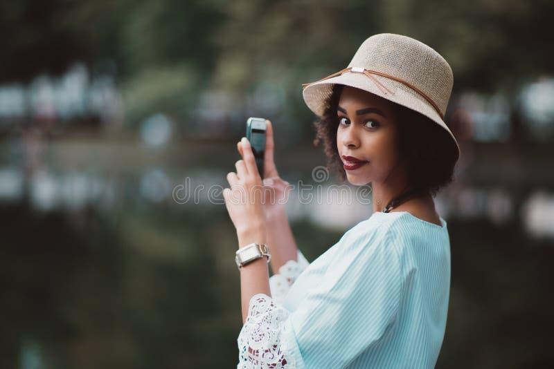 Afrikansk amerikanflickan fotograferar vatten av aftonsjön via fotografering för bildbyråer