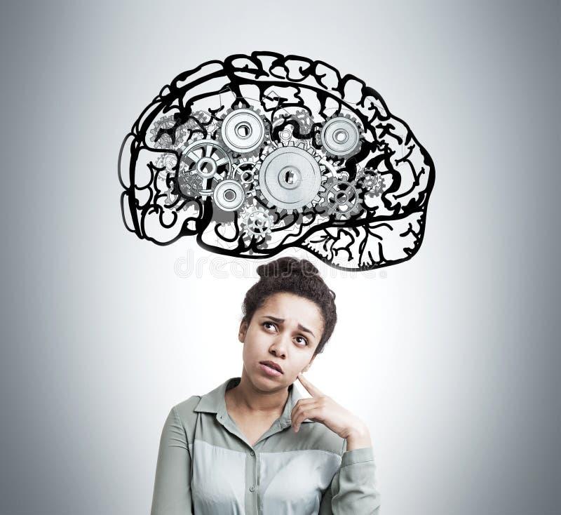 Afrikansk amerikanflickan med hjärnan och kugghjul skissar arkivbild
