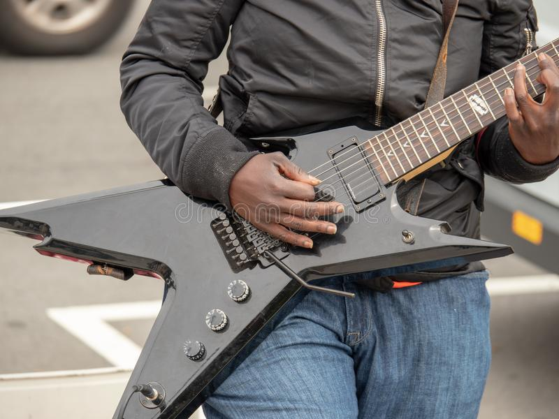 Afrikansk amerikangitarrist som klinkar den svarta elektriska gitarren royaltyfri foto