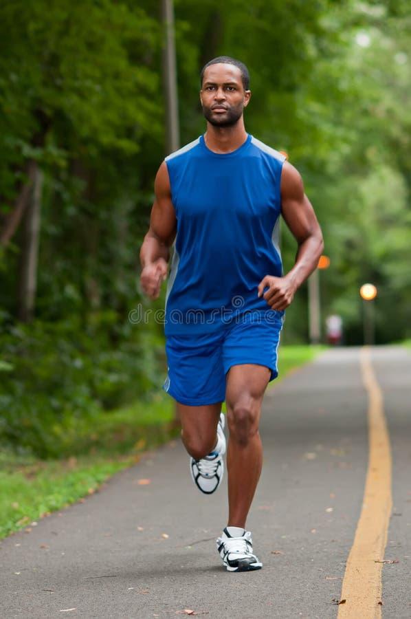 Afrikansk amerikanidrottsman nen Running On en skogsbevuxen bana arkivfoton