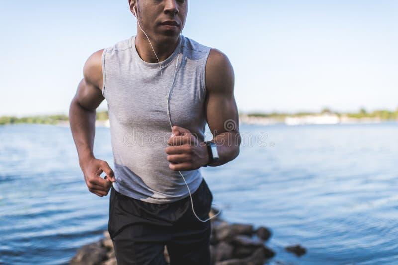 Afrikansk amerikanidrottsmanspring på flodstranden arkivfoton