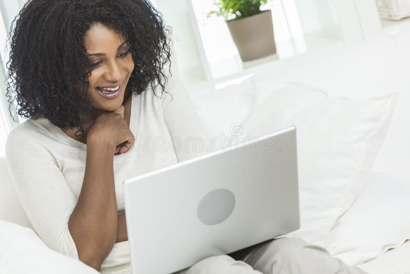 Afrikansk amerikankvinna, bärbar datordator hemma arkivfoto