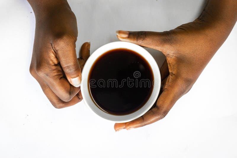 Afrikansk amerikankvinna båda händer som rymmer en vit kopp kaffe Svarta kvinnliga händer som rymmer en varm kopp kaffe med skum fotografering för bildbyråer