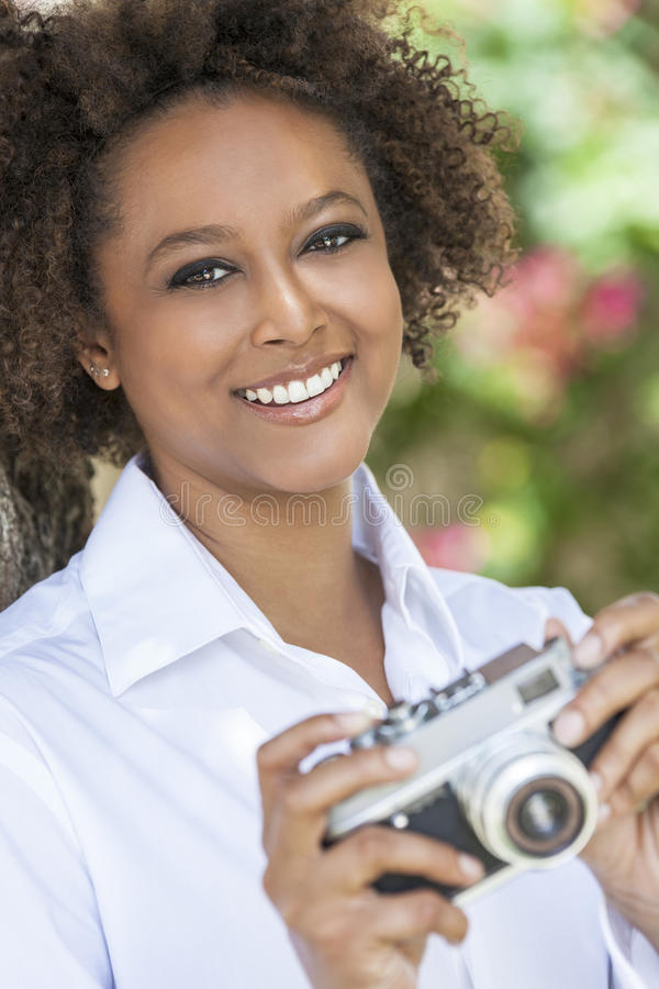Afrikansk amerikankvinna för blandat lopp med kameran arkivbilder