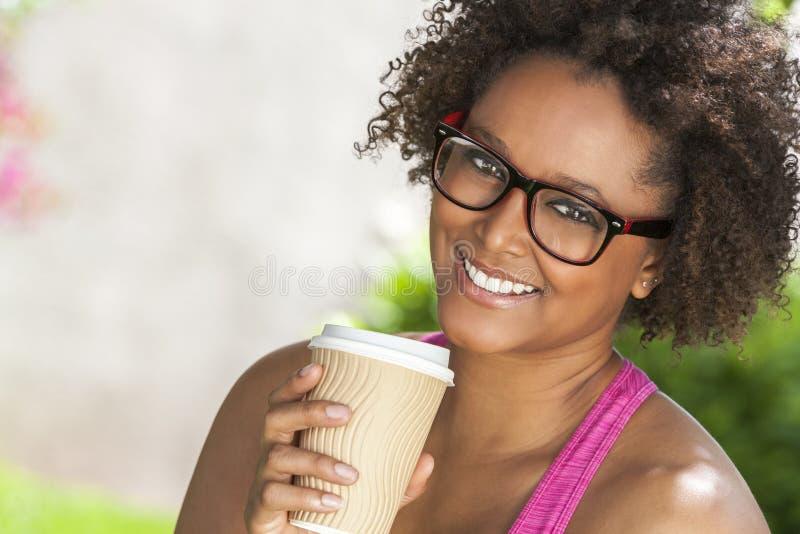 Afrikansk amerikankvinna i exponeringsglas som dricker kaffe arkivfoton