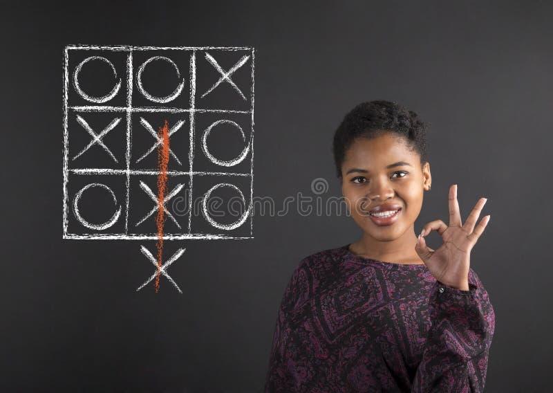 Afrikansk amerikankvinna med den perfekta handsignalen med ett diagram för muskelryckningtac-tå på svart tavlabakgrund arkivfoton