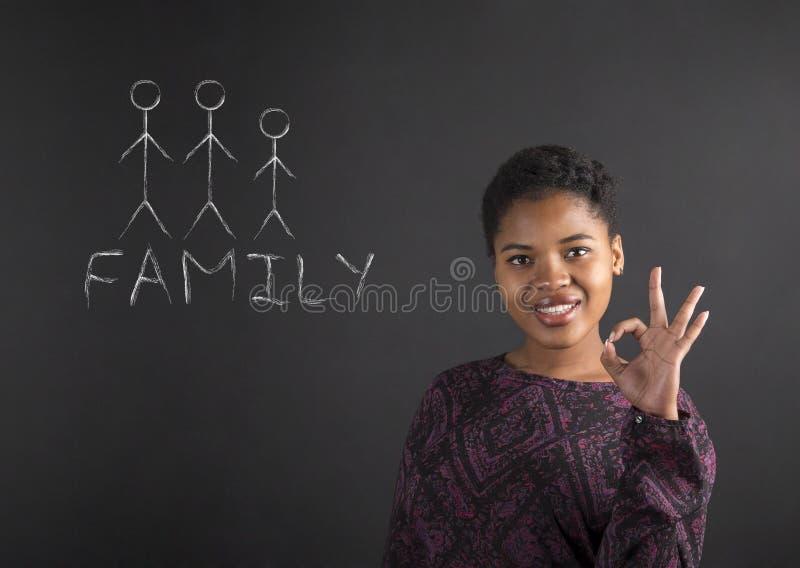 Afrikansk amerikankvinna med den perfekta handsignalen med familjdiagrammet på svart tavlabakgrund arkivbilder