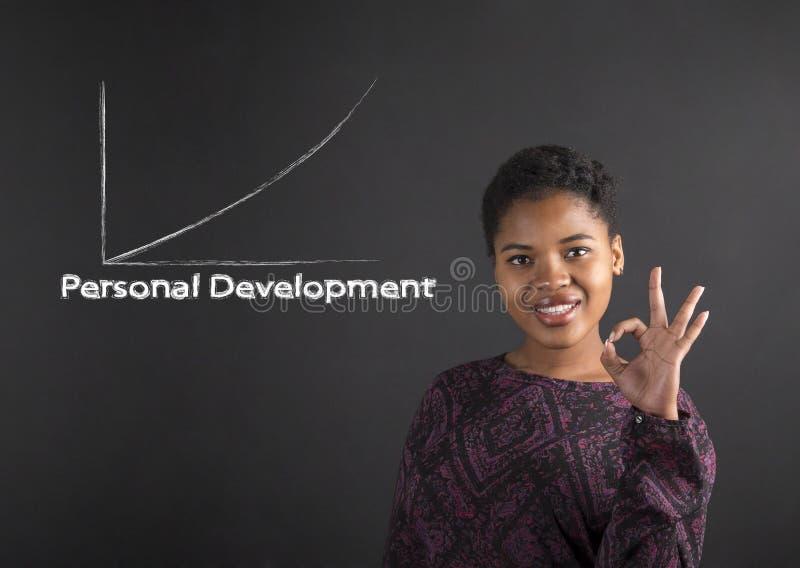 Afrikansk amerikankvinna med den perfekta handsignalen som visar personlig utveckling på svart tavlabakgrund arkivbild