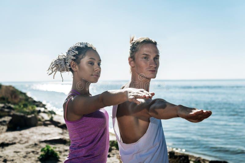 Afrikansk amerikankvinna med dreadlocks som gör yoga med hennes stiliga man arkivfoton