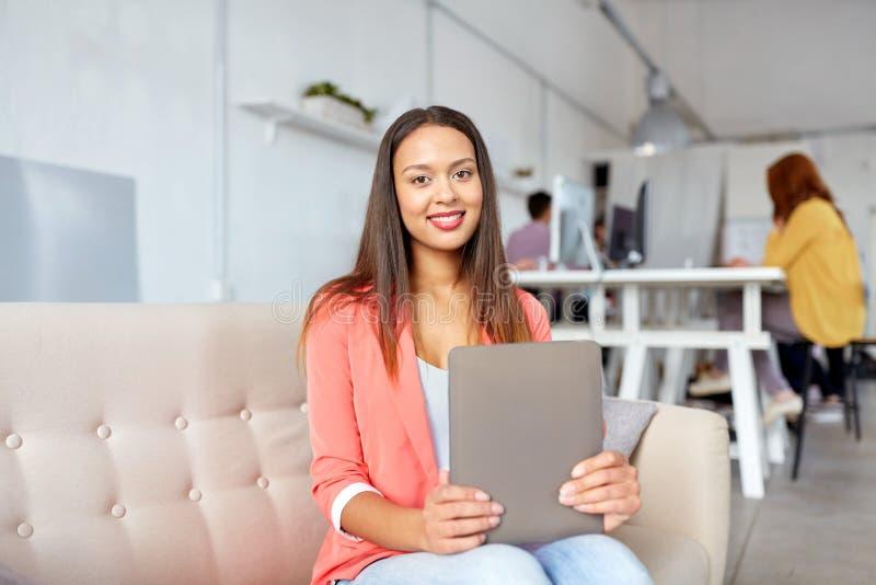 Afrikansk amerikankvinna med minnestavlaPC på kontoret fotografering för bildbyråer