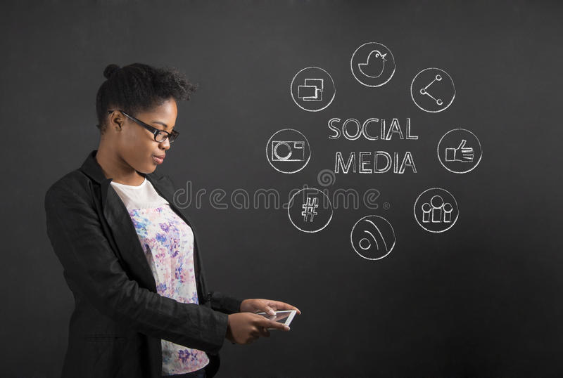 Afrikansk amerikankvinna med social nätverkande för minnestavla på svart tavlabakgrund arkivfoto