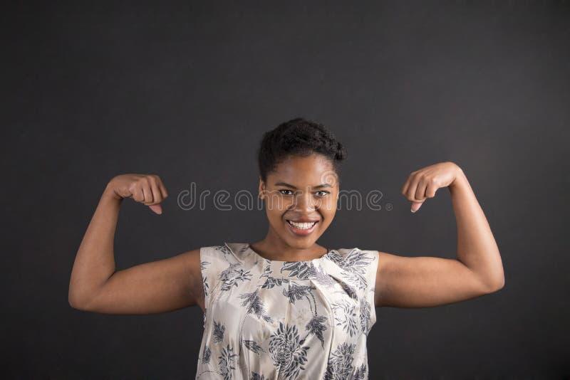 Afrikansk amerikankvinna med starka armar på svart tavlabakgrund fotografering för bildbyråer