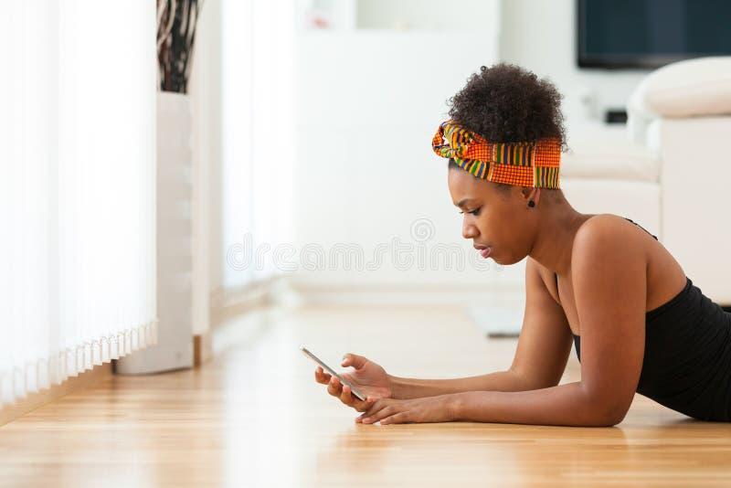 Afrikansk amerikankvinna som överför ett textmeddelande på en mobiltelefon royaltyfri fotografi
