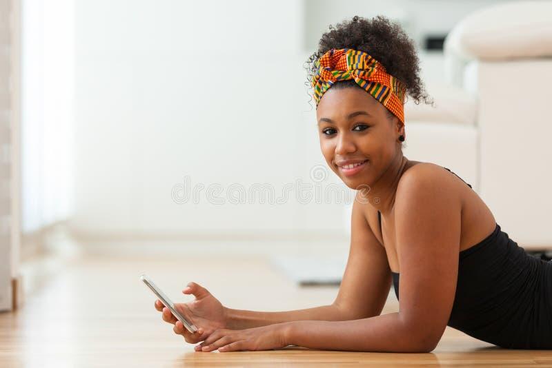 Afrikansk amerikankvinna som överför ett textmeddelande på en mobiltelefon fotografering för bildbyråer
