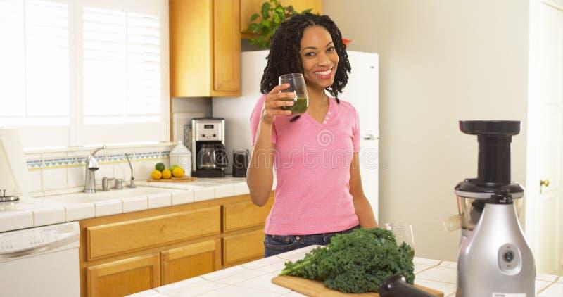 Afrikansk amerikankvinna som dricker nytt gjord fruktsaft royaltyfria foton