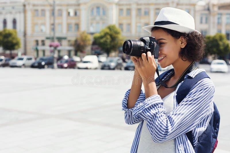 Afrikansk amerikankvinna som fotograferar med kameran på semester royaltyfri fotografi