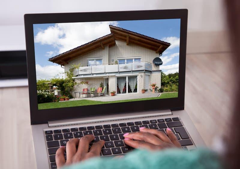 Afrikansk amerikankvinna som hemma väljer det nya huset på bärbara datorn royaltyfri fotografi