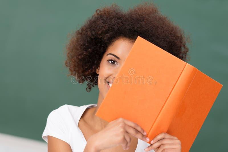 Afrikansk amerikankvinna som läser en bok arkivfoto