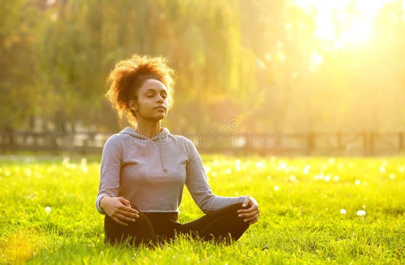 Afrikansk amerikankvinna som mediterar i natur arkivbild