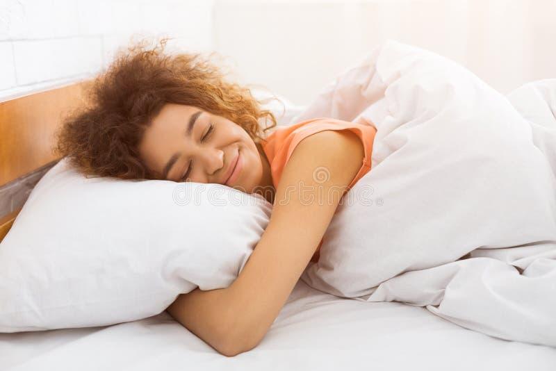 Afrikansk amerikankvinna som sover i säng som tycker om drömmar arkivfoton