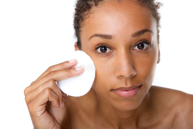 Afrikansk amerikankvinna som tar bort makeup med svampen arkivfoton