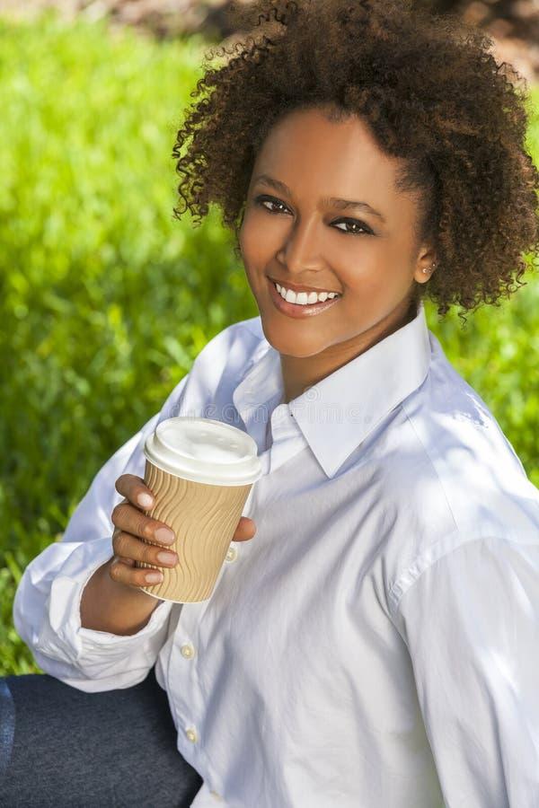 Afrikansk amerikankvinna som utanför dricker kaffe arkivfoton