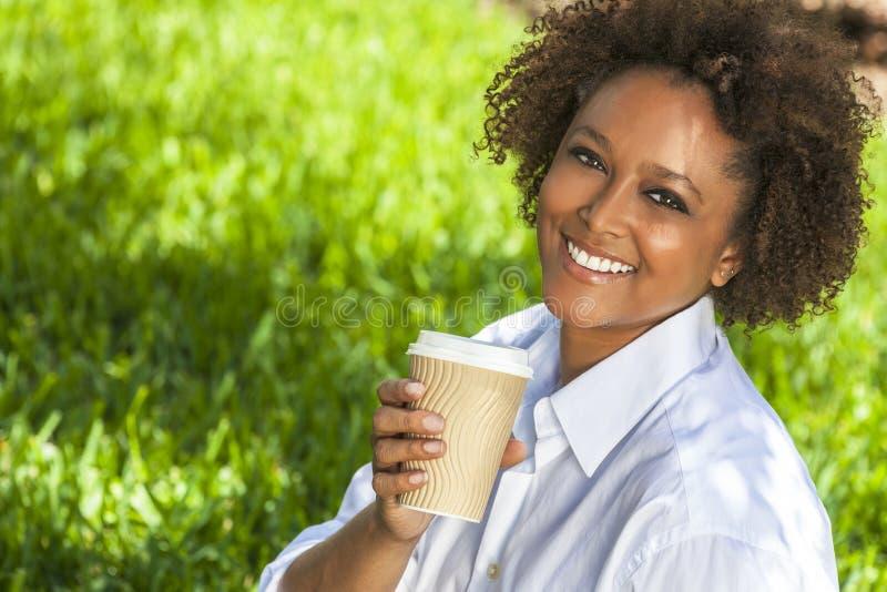 Afrikansk amerikankvinna som utanför dricker kaffe royaltyfria bilder