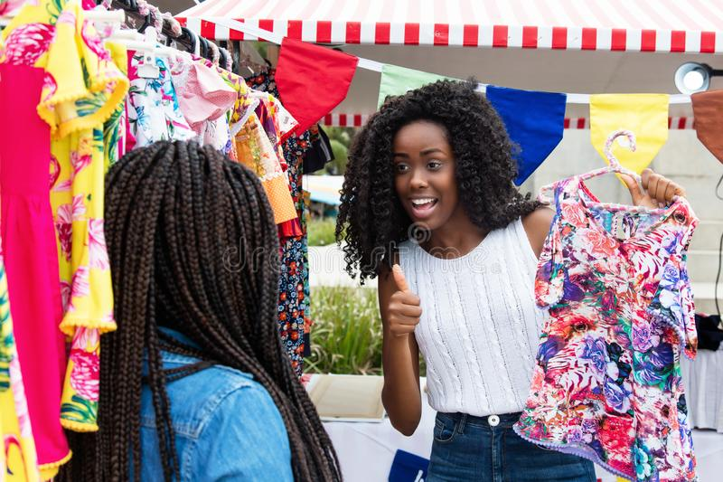 Afrikansk amerikankvinna som visar kläder till köparen på marknaden arkivfoto