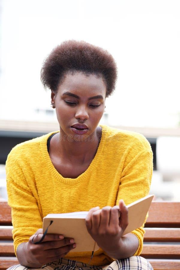 Afrikansk amerikankvinnaläsebok på den utomhus- bänken arkivbild