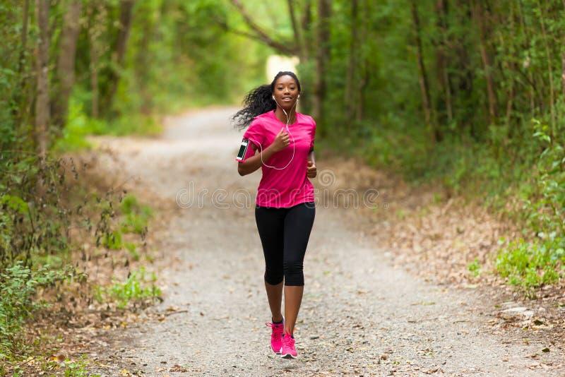 Afrikansk amerikankvinnalöpare som utomhus joggar - kondition, peopl arkivfoton