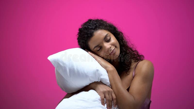 Afrikansk amerikankvinnan som sover p? kudden som isoleras p? rosa bakgrund, vilar royaltyfri fotografi